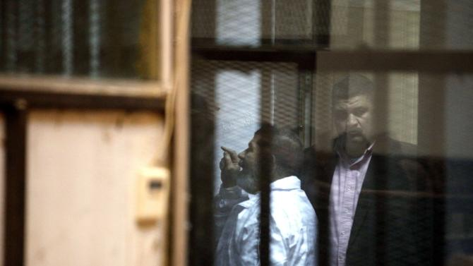 Former Egyptian President Mohamed Mursi talks with other Muslim Brotherhood members at a court in the outskirts of Cairo