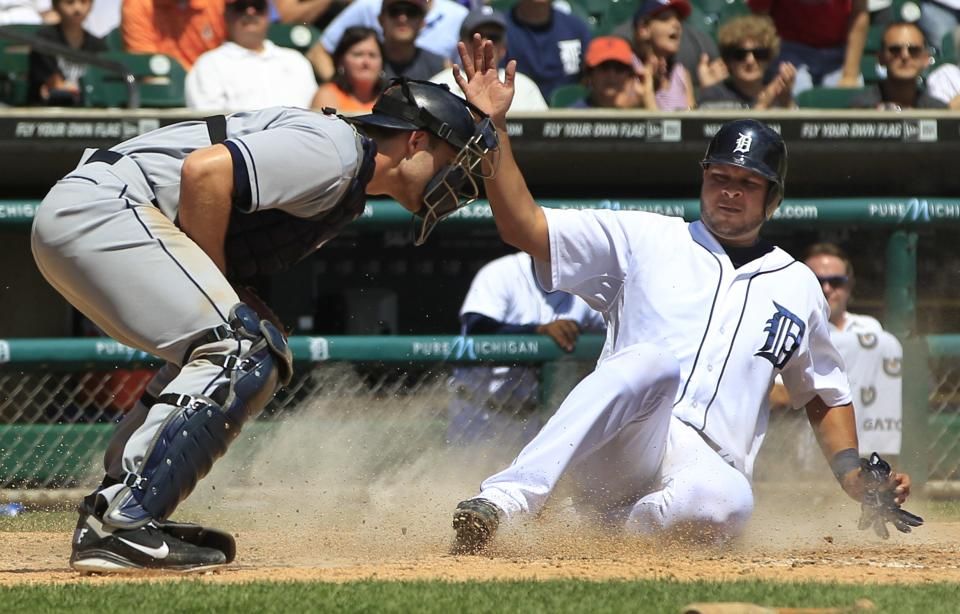 Detroit Tigers' Jhonny Peralta beats the throw to Cleveland Indians catcher Lou Marson on Alex Avila's single during the fourth inning of a baseball game in Detroit, Sunday, Aug. 5, 2012. (AP Photo/Carlos Osorio)
