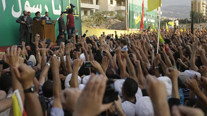 Hezbollah supporters raise their hands in support of their leader, Sheik Hassan Nasrallah, who speaks to a crowd of tens of thousands of supporters from a podium during a rally denouncing an anti-Islam film that has provoked a week of unrest in Muslim countries worldwide, in the southern suburb of Beirut, Lebanon, Monday Sept. 17, 2012. Nasrallah, who does not usually appear in public for fear of assassination, called for Monday's protests in Beirut, saying the U.S. must be held accountable for the film because it was produced in America. (AP Photo/Hussein Malla)
