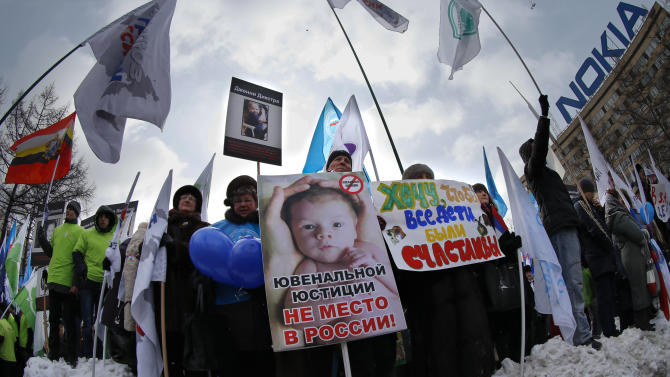 "Demonstrators hold posters reading ""There is no place for juvenile justice in Russia,"" ""I want all children be happy"" during a massive rally to back the ban on U.S. adoptions of Russian children in Moscow, Saturday, March 2, 2013. Russia voiced strong skepticism Saturday about the U.S. autopsy on Max Shatto, a 3-year-old adopted Russian boy in Texas and demanded further investigation as thousands rallied in Moscow to support the Kremlin ban on U.S. adoptions of Russian children. (AP Photo/Alexander Zemlianichenko)"