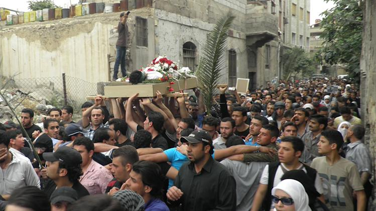 Anti-Syrian regime mourners shout slogans and carry the body of activist Nour al-Zahraa, 23, who was shot by Syrian security forces on Sunday, during his funeral procession, in the Kfar Suseh area, in Damascus, Syria, on Monday, April 30, 2012. (AP Photo)