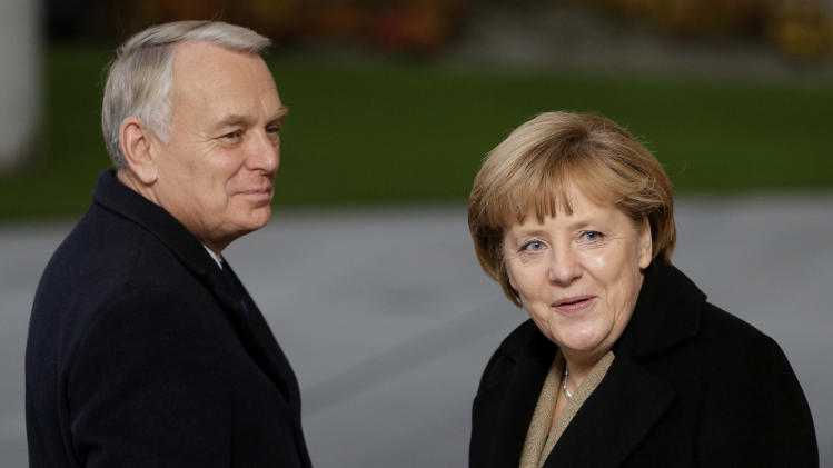 German Chancellor Angela Merkel, right, reacts as she welcomes the Prime Minister of France, Jean-Marc Ayrault, left, in front of the chancellery in Berlin, Germany, Thursday, Nov. 15, 2012. (AP Photo/Michael Sohn)