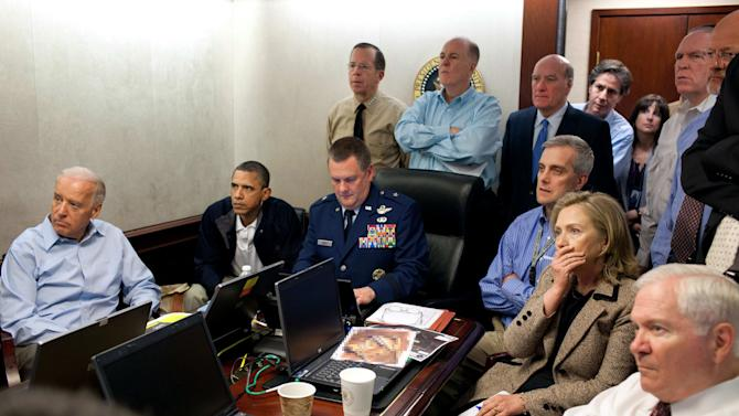"FILE - In this May 1, 2011, image released by the White House and digitally altered by the source to obscure the details of a document in front of Secretary of State Hillary Rodham Clinton, right with hand covering mouth, President Barack Obama, second from left, Vice President Joe Biden, left, Secretary of Defense Robert Gates, right, and members of the national security team watch an update of the mission against Osama bin Laden in the White House Situation Room in Washington. As the world now knows well Obama ultimately decided to launch the raid on the Abbottabad compound that killed bin Laden, though faced with a level of widespread skepticism from a veteran intelligence analyst, shared with other top-level officials, which nearly scuttled the raid. That process reflected a sea change within the U.S. spy community, one that embraces debate to avoid ""slam-dunk"" intelligence in tough national security decisions. (AP Photo/The White House, Pete Souza, File)"