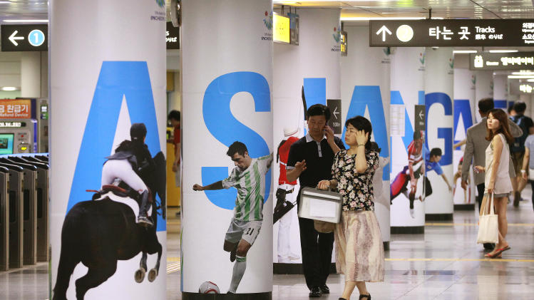 People pass by 2014 Asian Games posters at a subway station in Seoul, South Korea, Thursday, July 10, 2014. North Korea's Korean Central News Agency on Thursday said the North proposed a meeting at a border village next Tuesday to discuss its Asian Games participation.(AP Photo/Ahn Young-joon)