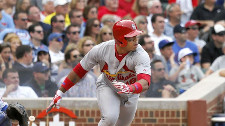 St. Louis Cardinals pinch hitter Oscar Taveras watches his RBI-single, scoring Mark Ellis, off Chicago Cubs relief pitcher Wesley Wright during the sixth inning of a baseball game Friday, July 25, 2014, in Chicago. (AP Photo/Charles Rex Arbogast)
