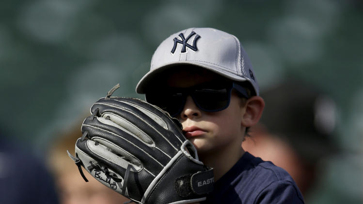 A young fan watches from atop an adults shoulders as the New York Yankees take in batting practice before a baseball game against the Texas Rangers, Monday, July 28, 2014, in Arlington, Texas. (AP Photo/Tony Gutierrez)