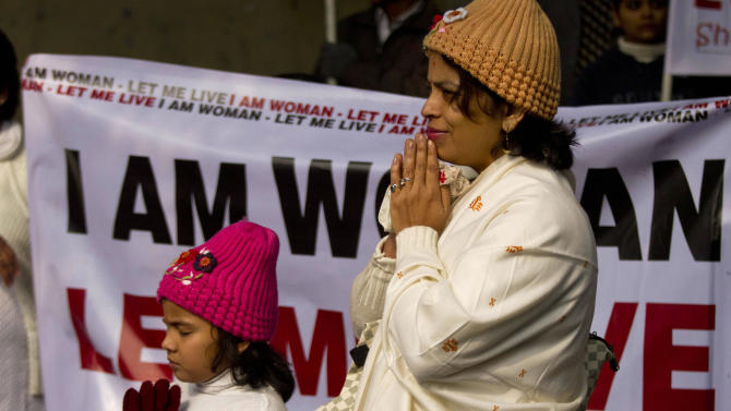 An Indian woman and her daughter pray as they take part in a silent protest to mourn the death of a gang rape victim in New Delhi, India, Tuesday, Jan. 1, 2013. The gang-rape and killing of a New Delhi student has set off an impassioned debate about what India needs to do to prevent such a tragedy from happening again. The country remained in mourning Tuesday, three days after the 23-year-old physiotherapy student died from her internal wounds in a Singapore hospital. (AP Photo/ Dar Yasin)
