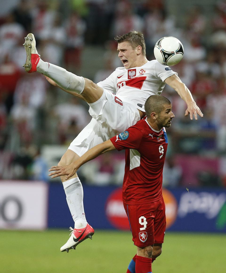 Poland's Lukasz Piszczek falls over Czech Republic's Jan Rezek  during the Euro 2012 soccer championship Group A match between Czech Republic and Poland in Wroclaw, Poland, Saturday, June 16, 2012. (AP Photo/Jon Super)