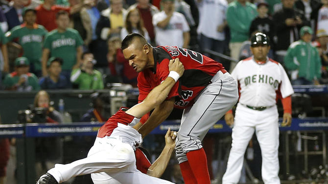 Canada's Tyson Gillies, right and Mexico's Alfredo Aceves fight during the ninth inning of a World Baseball Classic game, Saturday, March 9, 2013, in Phoenix. (AP Photo/Matt York)