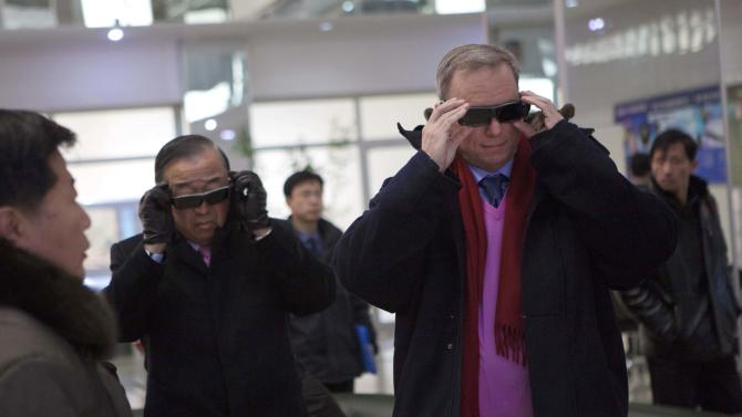 "Executive Chairman of Google, Eric Schmidt, right, tries on 3-D glasses as he looks at North Korean-developed computer technology during a tour of the Korean Computer Center in Pyongyang, North Korea on Wednesday, Jan. 9, 2013. At left is Kun ""Tony"" Namkung, a North Korea's expert and member of the traveling delegation. (AP Photo/David Guttenfelder)"