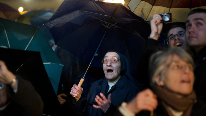 A nun reacts after white smoke billowed from the chimney on the Sistine Chapel indicating that a new pope has been elected in St. Peter's Square at the Vatican, Wednesday, March 13, 2013. Argentine Cardinal Jorge Bergoglio, who chose the name of Pope Francis, is the 266th pontiff of the Roman Catholic Church. (AP Photo/Emilio Morenatti)