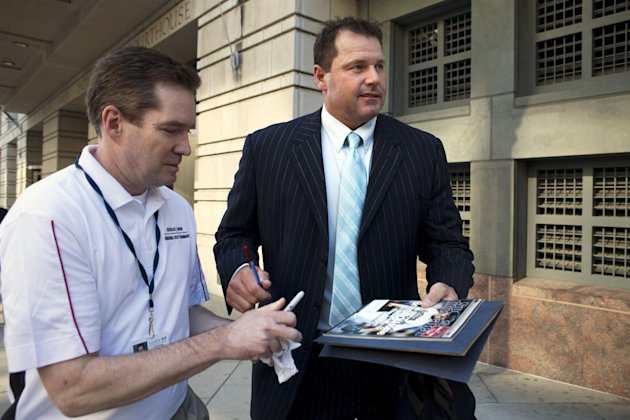 Roger Clemens, right, signs an autograph for baseball fan Dwayne Cantrell, as Clemens leaves federal court in Washington, Thursday, May 10, 2012. Clemens is on trial for allegedly lying to Congress in