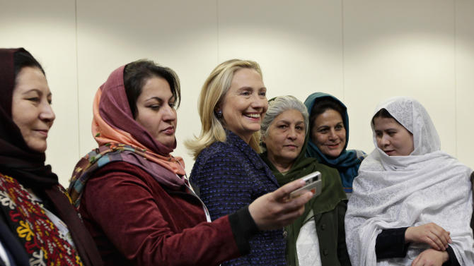 U.S. Secretary of State Hillary Rodham Clinton poses for photos with an Afghan women's civil society delegation during an international conference on the future of Afghanistan, Monday, Dec. 5, 2011, in Bonn, Germany. Representatives of more than 90 countries and organizations are gathering to discuss the future of Afghanistan after the eventual withdrawal of foreign military forces.  (AP Photo/J. Scott Applewhite, Pool)