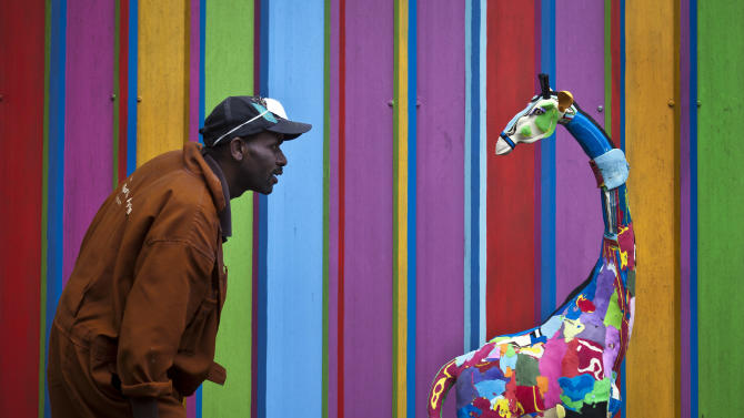 In this photo taken Monday, April 29, 2013, carver Jackson Mbatha, 40, poses next to a an unfinished large toy giraffe he is making from pieces of discarded flip-flops, in front of a painted workshop wall at the Ocean Sole flip-flop recycling company in Nairobi, Kenya. The company is cleaning the East African country's beaches of used, washed-up flip-flops and the dirty pieces of rubber that were once cruising the Indian Ocean's currents are now being turned into colorful handmade giraffes, elephants and other toy animals. (AP Photo/Ben Curtis)