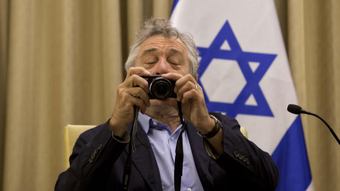U.S. actor Robert De Niro takes a photo of members of the media prior to his meeting with Israel's President Shimon Peres at the President's residence in Jerusalem Tuesday, June 18, 2013. (AP Photo/Sebastian Scheiner)