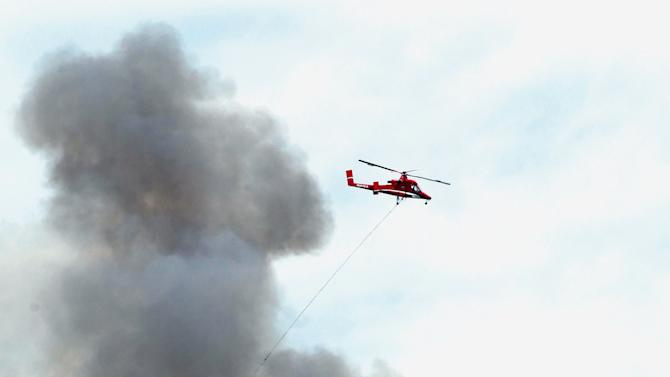 A firefighting helicopter flies past a plume of smoke on its way to refilling its bucket while battling the Waldo Canyon wildfire west of Manitou Springs, Colo., on Monday, June 25, 2012. (AP Photo/Ed Andrieski)