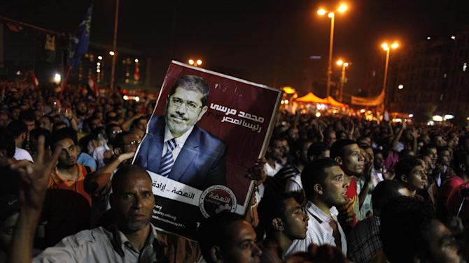 "Egyptian Muslim Brotherhood supporters chant slogans and one carries a poster with a picture of presidential candidate, Mohammed Morsi and Arabic that reads ""Mohammed Morsi, president for Egypt, revival is the will of the people,"" during an anti-ruling military council demonstration in Tahrir Square, Cairo, Egypt Wednesday, June 20, 2012. Authorities delayed Thursday's planned announcement of the winner of Egypt's presidential election, likely for several days, hiking tension as allegations of fraud swirled and each candidate declared he was the victor. (AP Photo/Nasser Nasser)"