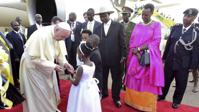 Pope Francis is welcomed by President of Uganda, Yoweri Museveni, at right with hat, at Entebbe International Airport some 40 km from Uganda Capital Kampala  Friday, Nov. 27 2015.  Pope Francis is in Africa for a six-day visit that is taking him to Kenya, Uganda and the Central African Republic. (AP Photo/Stephen Wandera)