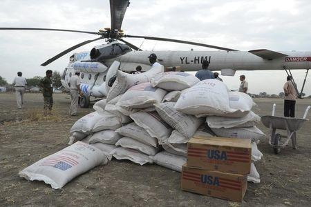 Sacks of food are unloaded from a UN helicopter in Pibor