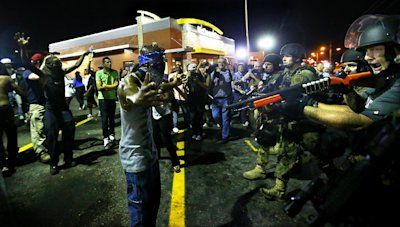 Police officers move in to arrest protesters as they push and clear crowds out of the West Florissant Avenue area in Ferguson, Mo. early Wednesday, Au...