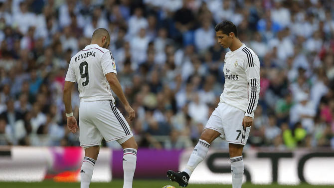 Real Madrid's Cristiano Ronaldo, right, restarts the game with teammate Karim Benzema, left, after Barcelona's Neymar goal during a Spanish La Liga soccer match between Real Madrid and FC Barcelona at the Santiago Bernabeu stadium in Madrid, Spain, Saturday, Oct. 25, 2014