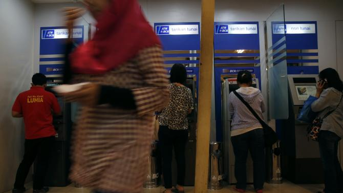 A woman walks in front of Bank Central Asia ATMs in Jakarta