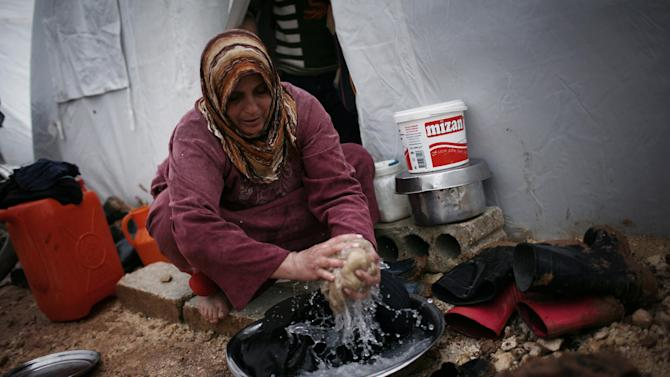 A displaced Syrian woman washes some clothes in front of her tent in the Azaz camp for displaced people, north of Aleppo province, Syria, Monday, Feb. 18, 2013. According to Syrian activists the number of people in the Azaz camp has grown by 3,000 in the last weeks due to heavier shelling by government forces. (AP Photo/Manu Brabo)