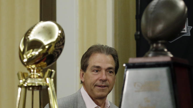 Alabama head coach Nick Saban walks past some national championship trophies to a BCS National Championship college football game news conference Tuesday, Jan. 8, 2013, in Ft. Lauderdale, Fla. Alabama defeated Notre Dame 42-14 Monday night to win the national championship. (AP Photo/Morry Gash)