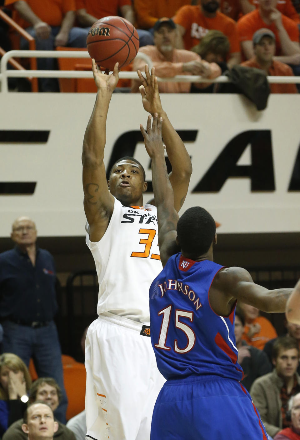 Oklahoma State guard Marcus Smart (33) shoots over Kansas guard Elijah Johnson (15) during the first half of an NCAA college basketball game in Stillwater, Okla., Wednesday, Feb. 20, 2013. (AP Photo/Sue Ogrocki)