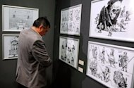 A visitor looks at drawings by Kallaugher during an exhibition at the National Museum of Contemporary Art in Bucharest. Kallaugher's satirical drawings for The Economist and US daily The Baltimore Sun are featured in an exhibition that opened this week at the National Museum of Contemporary Art in the Romanian capital