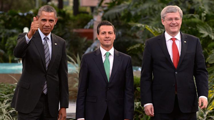 President Barack Obama, left, gives a thumbs up as he poses for photos with Mexico's President Enrique Pena Nieto, center, and Canada's Prime Minister Stephen Harper at the North American Leaders Summit in Toluca, Mexico, Wednesday, Feb. 19, 2014. The leaders met in part to highlight the economic cooperation that has grown since the North American Free Trade Agreement (NAFTA) joined the U.S., Canada and Mexico 20 years ago. (AP Photo/Canadian Press, Sean Kilpatrick)
