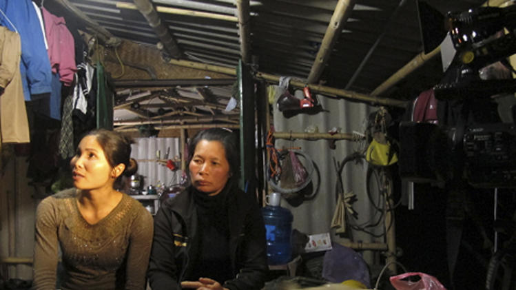 In this photo taken Monday, April 1, 2013, Pham Thi Bau, left, and Nguyen Thi Thuong talk to a reporter in their home close to Haiphong, Vietnam. The two women were among six family members to go on trial on Tuesday on charges relating to their violent resistance to a land eviction last year. Thi Thuon's husband Doan Van Vuon is accused of masterminding a defense of his property that saw family members detonate homemade mines and fire off shotguns, injuring seven police and army officers. (AP Photo/Chris Brummitt)