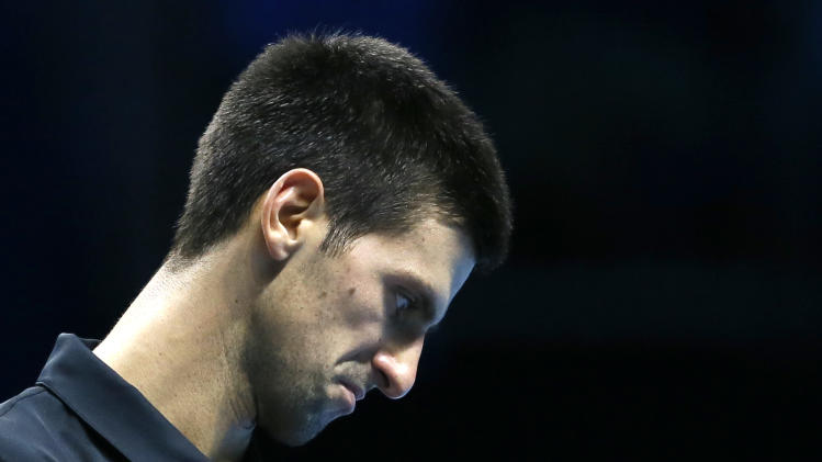 Novak Djokovic of Serbia checks his strings after he plays a return to Tomas Berdych of the Czech Republic during their singles tennis match at the ATP World Tour Finals in London Friday, Nov. 9, 2012. (AP Photo/Kirsty Wigglesworth)