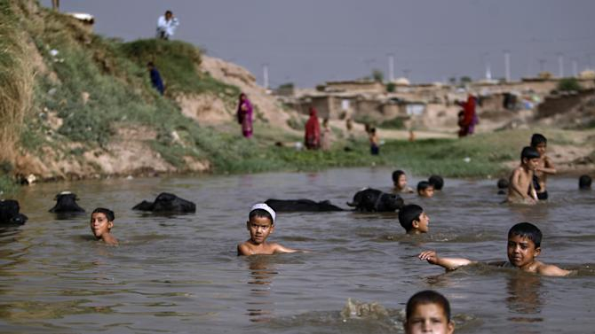 In this Tuesday, June 5, 2012, photo, Afghan refugee boys soak in a polluted a stream to beat the heat, in a slum area on the outskirts of Islamabad, Pakistan.  Hundreds of thousands of Afghan refugees are in limbo as Pakistan, increasingly frustrated with hosting the world's largest and longest-running refugee population, weighs whether to renew their refugee status by the end of this year. A large-scale return of the 1.7 million Afghan refugees currently living in Pakistan would be a massive problem for Afghanistan at a time when it's already struggling to maintain security in the face of an American troop withdrawal. But Pakistan increasingly seems to be angry at a refugee population that many feel has overstayed its welcome. (AP Photo/Muhammed Muheisen)