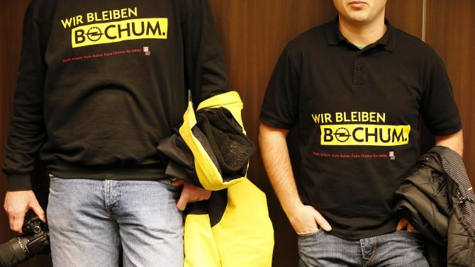 Opel employees wear T-Shirts that read: 'we stay Bochum' in Bochum, Germany, Monday, Dec. 10, 2012. Opel plans to stop car production in 2016 in Bochum. But Opel says the company's warehouse in Bochum will continue to employ people after 2016 and may be expanded. The company also is negotiating with employee representatives to produce components at the site. Opel belongs to the US company General Motors.(AP Photo/Frank Augstein)