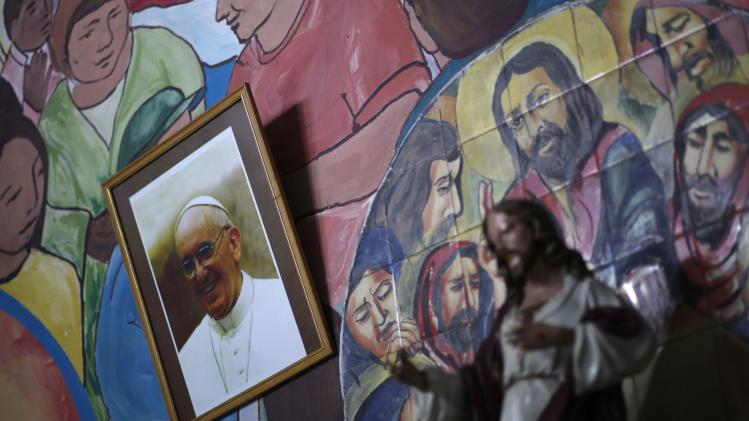 A picture of Pope Francis is seen next to a statue of Jesus Christ at the altar of the Virgen de Caacupe Catholic Church during Good Friday celebrations at Villa 21 slum in Buenos Aires