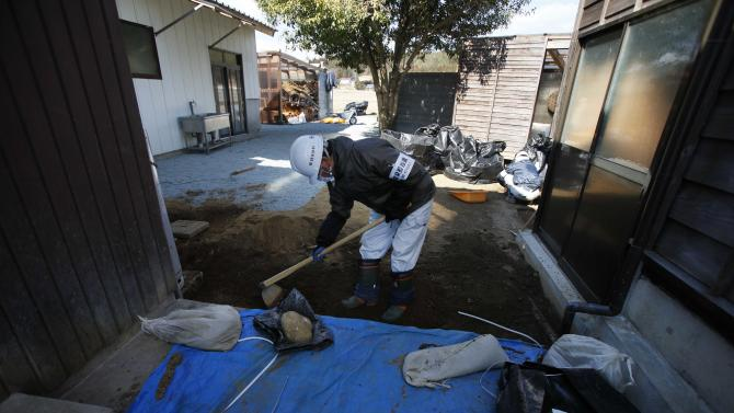 In this Tuesday, March 5, 2013, a worker shovels the top layer of radiation-contaminated soil at a house in Naraha, just outside the exclusion zone surrounding the Fukushima Dai-ichi nuclear plant in Japan. Decontamination efforts have begun in the town but resident have not been allowed to return for more than brief visits. Two years after the triple calamities of earthquake, tsunami and nuclear disaster ravaged Japan's northeastern Pacific coast, radioactive and chemical contamination remains a threat. (AP Photo/Greg Baker)