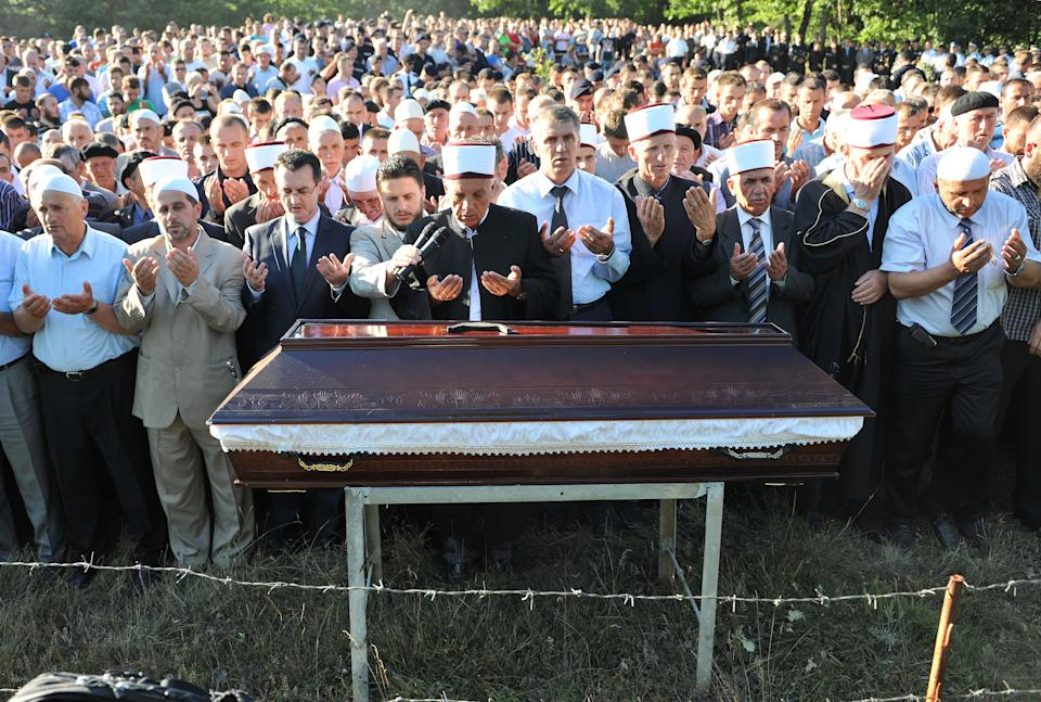 Mourners pray during the funeral of the slain officer Enver Zymberi in the village of Dubovc on Wednesday, July 27, 2011. Zymberi was killed in an ambush during a police operation to take control of two border crossings with Serbia in Kosovo's Serb-dominated north.(AP Photo/Visar Kryeziu)