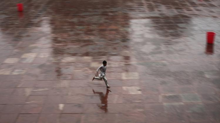 A Muslim boy runs for cover after offering evening prayers, as it rains on the last day of the holy fasting month of Ramadan in India, at the Jama Masjid in the old quarters of Delhi