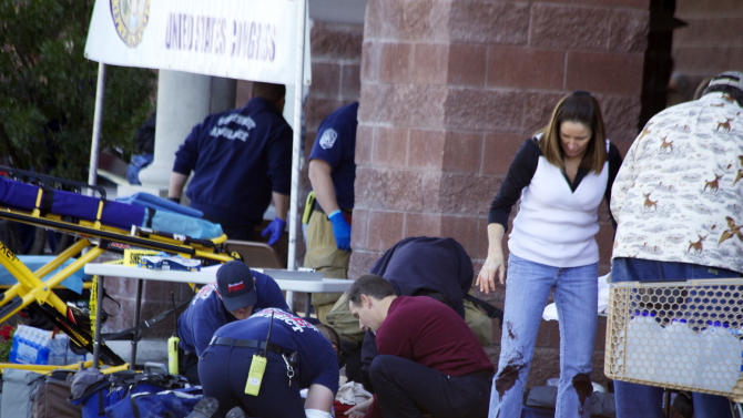 FILE - Emergency personnel attend to a shooting victim  outside a shopping center in Tucson, Ariz. in this Saturday, Jan. 8, 2011 file photo taken where U.S. Rep. Gabrielle Giffords, D-Ariz., and others were shot as the congresswoman was meeting with constituents. Hundreds of pages of police reports in the investigation of the Tucson shooting rampage that wounded former Rep. Gabrielle Giffords are being released Wednesday, March 27, 2013 marking the public's first glimpse into documents that authorities have kept private since the attack more than two years ago.  (AP Photo/James Palka, File)