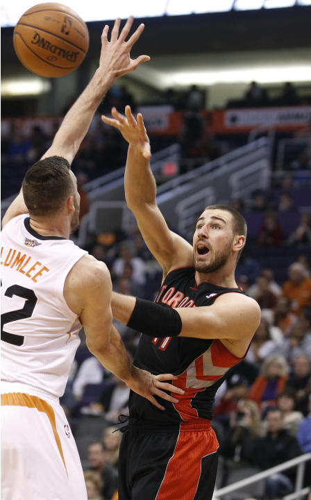 Toronto Raptors' Jonas Valanciunas, right, of Lithuania, passes around the defense of Phoenix Suns' Miles Plumlee during the first half of an NBA basketball game on Friday, Dec. 6, 2013, in Ph