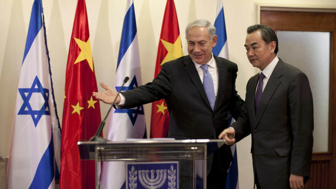 Israeli Prime Minister Benjamin Netanyahu, left, directs Chinese Foreign Minister Wang Yi to a podium for a press conference before their meeting at the prime minister's office in Jerusalem, Wednesday, Dec. 18, 2013. (AP Photo/Abir Sultan, Pool)