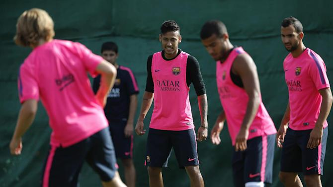 FC Barcelona's Neymar, center, from Brazil, trains with team mates during a training session at the Sports Center FC Barcelona Joan Gamper in San Joan Despi in Barcelona, Spain, Friday, Aug. 15, 2014. Luis Suarez also trained with his Barcelona teammates on Friday after his ban for biting an opponent at the World Cup was softened but not shortened.The Court of Arbitration for Sport ruled Thursday that the Uruguay forward, who recently left Liverpool for Barcelona, deserves his four-month ban from playing official matches for both his club and his country. (AP Photo/Emilio Morenatti )