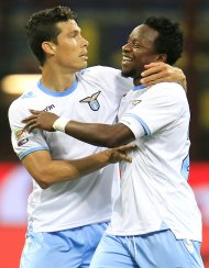 Lazio's Ogenyi Onazi (R) celebrates with team mate Hernanes after scoring their third goal against Inter Milan during their Italian Serie A soccer match at the San Siro stadium in Milan May 8, 2013. REUTERS/Alessandro Garofalo (ITALY - Tags: SPORT SOCCER)