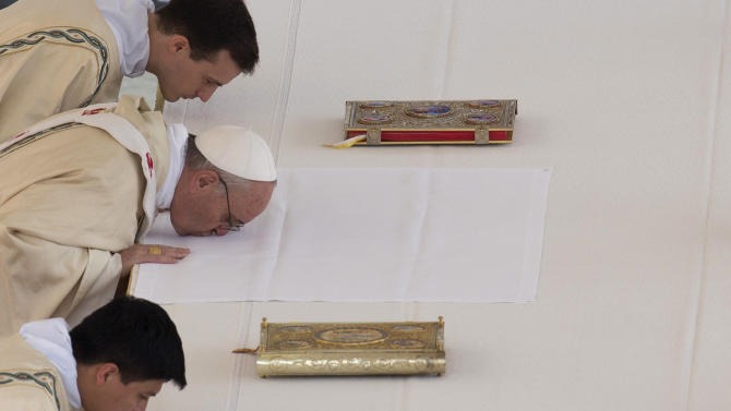 Pope Francis, middle, kisses the altar as he arrives to celebrate his first canonization ceremony in St. Peter's Square at the Vatican, Sunday, May 12, 2013. The pontiff will canonize Antonio Primaldo and his companions, also known as the Martyrs of Otranto, Laura di Santa Caterina da Siena Montoya of Colombia, and Maria Guadalupe Garcia Zavala of Mexico in a ceremony at the Vatican on Sunday. (AP Photo/Alessandra Tarantino)