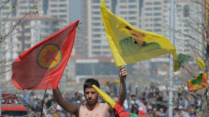 A man stands high above other demonstrators waving PKK flag and an image of jailed Kurdish rebel leader Abdullah Ocalan, in southeastern Turkish city of Diyarbakir, Turkey, Thursday, March 21, 2013, as Ocalan called Thursday for an immediate cease-fire and for thousands of his fighters to withdraw from Turkish territory, a major step toward ending the fighting for self-rule for Kurds in southeastern Turkey, one of the world's bloodiest insurgencies lasting nearly 30-years and costing tens of thousands of lives. (AP Photo)