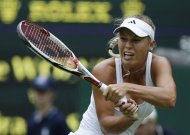 Caroline Wozniacki of Denmark returns a shot to Tamira Paszek of Austria during a first round women's singles match at the All England Lawn Tennis Championships at Wimbledon, England, Tuesday, June 26, 2012. (AP Photo/Anja Niedringhaus)