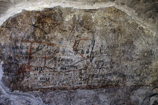 An ancient graffiti, in background red, covered by tourist's graffiti, is seen inside a gallery of Rome's Colosseum, Friday, Jan. 18, 2013. A long-delayed restoration of the Colosseum's only intact in