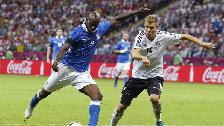 Italy's Mario Balotelli, left, kicks the ball past Germany's Holger Badstuber during the Euro 2012 soccer championship semifinal match between Germany and Italy in Warsaw, Poland, Thursday, June 28, 2012. (AP Photo/Jon Super)