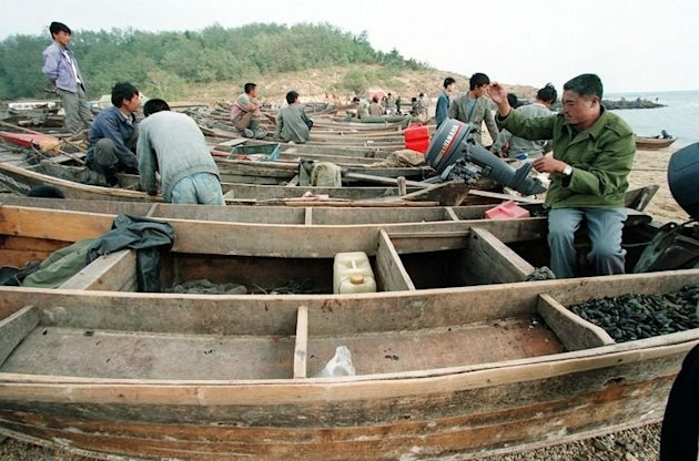 Chinese fishermen tend to their boats in Dalian, northeastern China on September 27, 1997